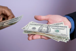 Businessman holding out hand for money, close-up